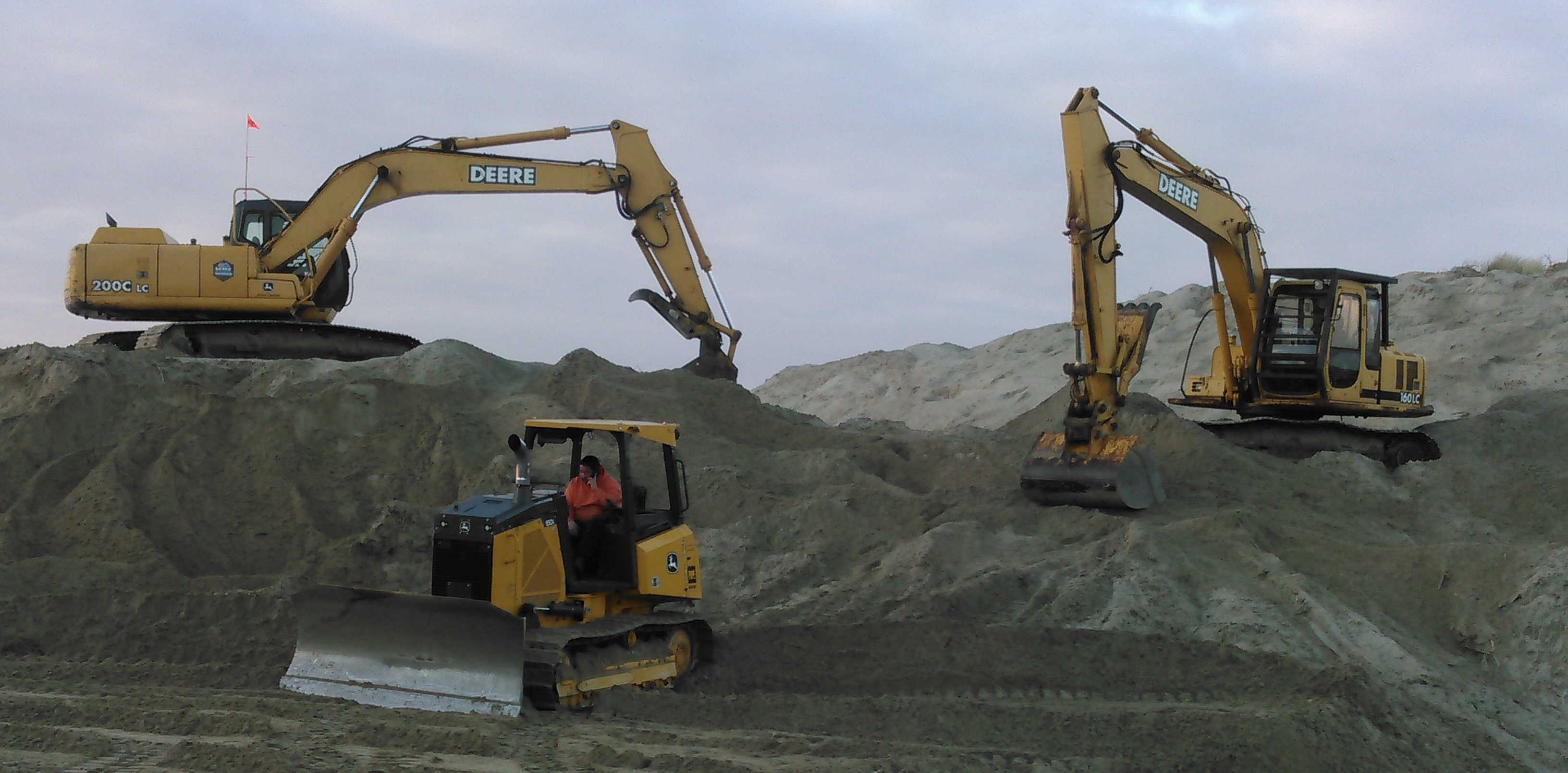 A hillside of sand and dirt with heavy machinery present.